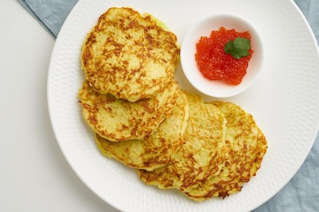 Pancake di zucchine con patate e caviale rosso, primo piano di vista superiore di dieta di cheto di fodmap