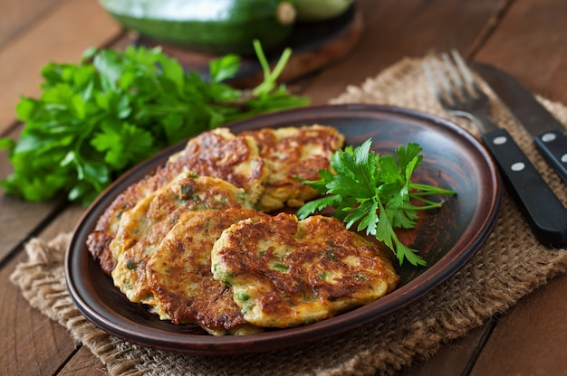 Pancake di zucchine con prezzemolo su una tavola di legno