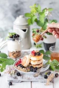 Pancake fatti in casa con frutti di bosco e sveglia su bianco in legno