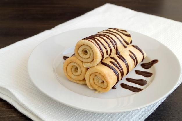 Pancake fatti in casa ritorti con cioccolato su un piatto bianco.