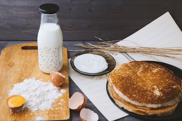 Pancake freschi e caldi in una padella, uova, latte, farina su una tavola di legno.
