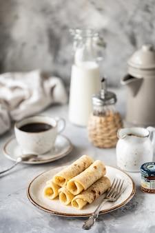 Pancake impilati su un piatto con una tazza di caffè e una bottiglia di latte