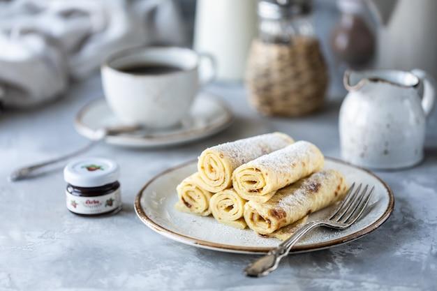 Pancake impilati su un piatto su un tavolo bianco con una tazza di caffè e una bottiglia di latte