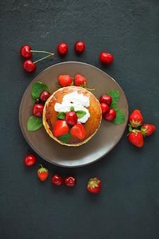 Pancake in un piatto con fragole, panna montata, menta, miele e ciliegia su uno sfondo nero scuro