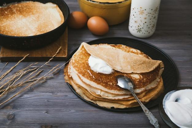 Pancake in una padella e ingredienti per loro su una tavola di legno