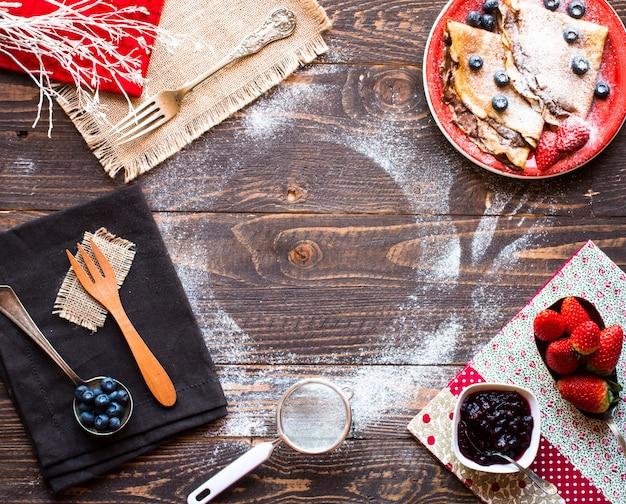 Pancake o crepes freschi delle fragole con le bacche e il cioccolato su fondo di legno
