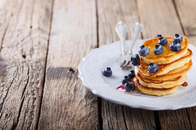 Pancake piegato pila di miele liquido e mirtilli freschi