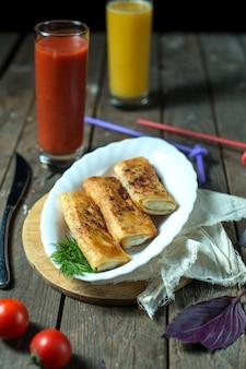 Pancake rotolati vista laterale con succo di pomodoro e pomodori