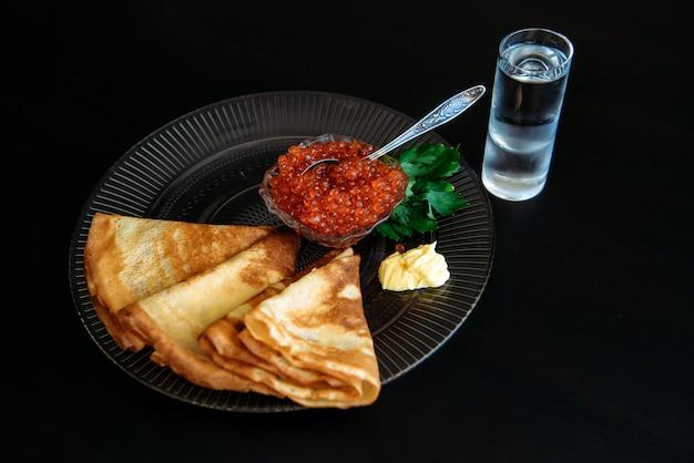Pancake russi con caviale rosso e burro in zolla trasparente vicino a vetro di vodka del ghiaccio isolata sul nero