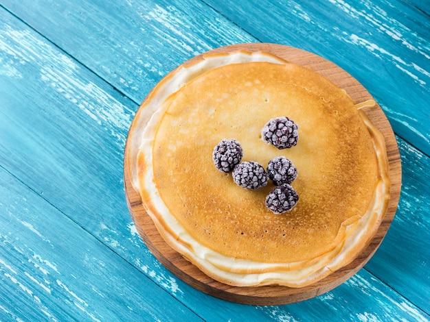 Pancake russi su un piatto di legno su una tavola azzurrata con le more congelate.