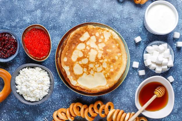 Pancake russo blini con marmellata di lamponi, miele, panna fresca e caviale rosso, zollette di zucchero, ricotta, bubliks su oscurità