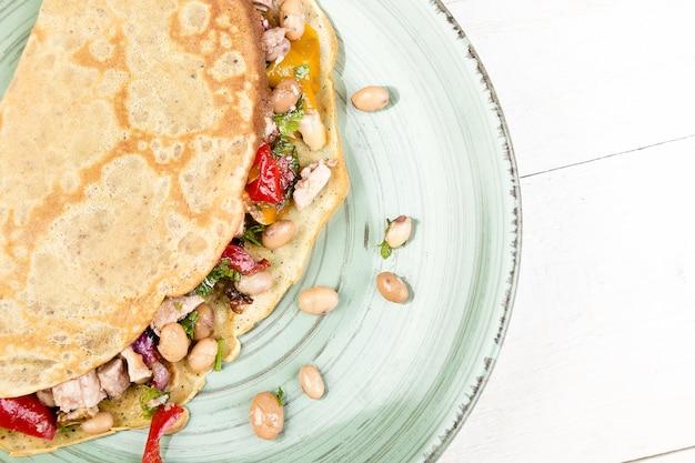 Pancake salato al grano saraceno con fagioli bianchi, peperone rosso e giallo, prezzemolo e pollo.