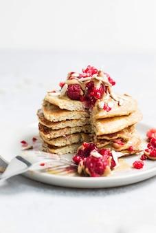 Pancake saporiti con il primo piano dei girasoli e dei lamponi su bianco