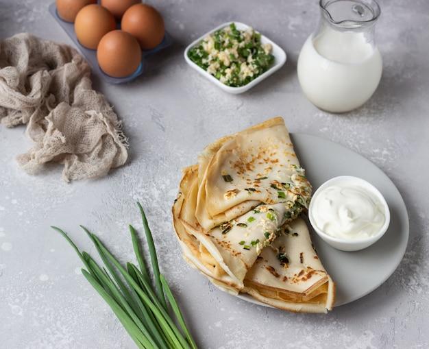 Pancake sottili con uovo, cipolla verde e yogurt naturale o panna acida