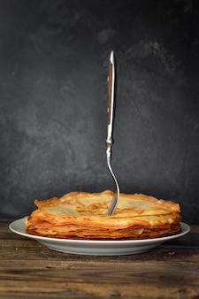 Pancake sottili isolati su un tavolo di legno scuro. pancakes e forcella vista laterale. spazio libero per il testo.
