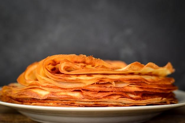 Pancake sottili isolati su un tavolo di legno scuro. spazio libero per il testo.