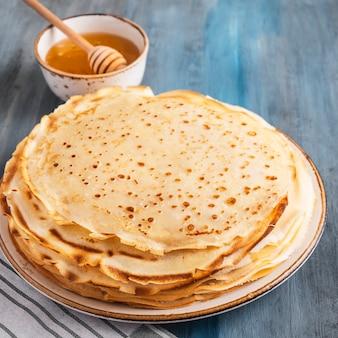 Pancake sottili su un piatto con miele. avvicinamento.