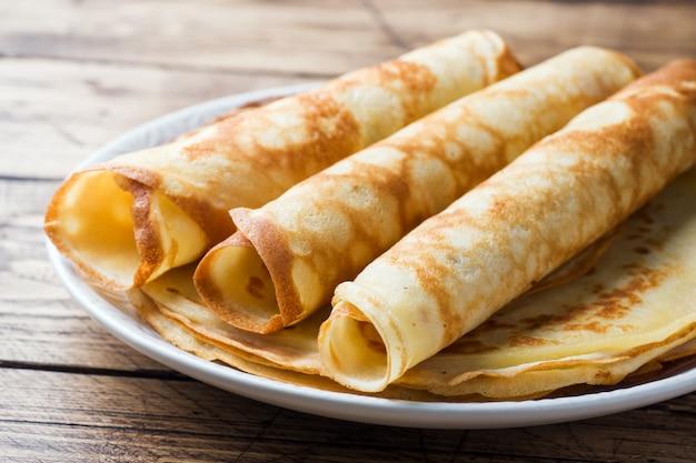 Pancake sottili su un piatto. fondo in legno avvicinamento.
