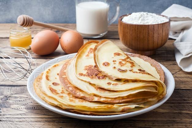 Pancake sottili su un piatto. fondo in legno ingredienti per cucinare uova, latte, farina.