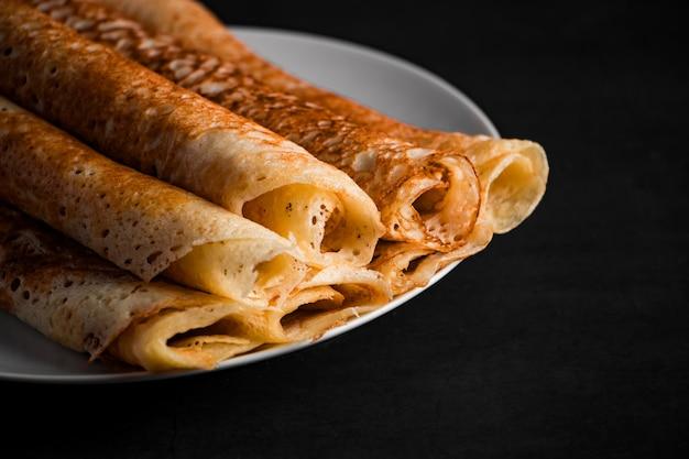 Pancake sottili su un piatto su uno sfondo nero, cibo tradizionale russo.