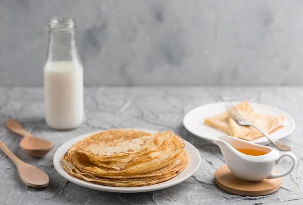 Pancake sul piatto con la bottiglia per il latte