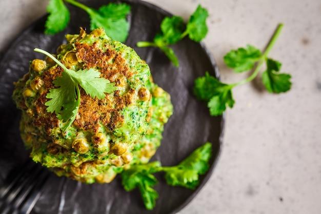 Pancake verdi del pisello e dei broccoli sulla banda nera, vista superiore. concetto di cibo sano vegan.