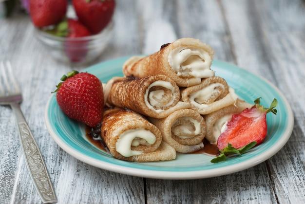 Pancakes arrotolati con fragole. prima colazione.