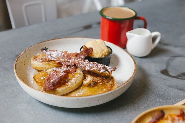 Pancakes con burro e sciroppo d'acero con pancetta croccante e gelato alla vaniglia.