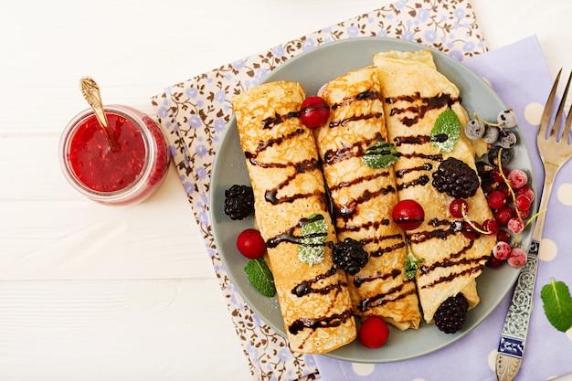 Pancakes con cioccolato, marmellata e frutti di bosco. gustosa colazione disteso. vista dall'alto