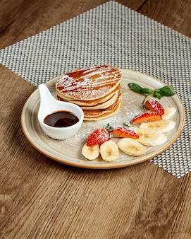Pancakes con fette di frutta e marmellata