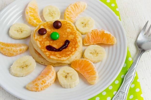 Pancakes con frutta e marmellata per i bambini. concetto di colazione