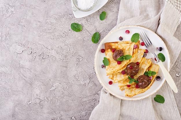 Pancakes con frutti di bosco e cioccolato decorati con foglie di menta. gustosa colazione vista dall'alto