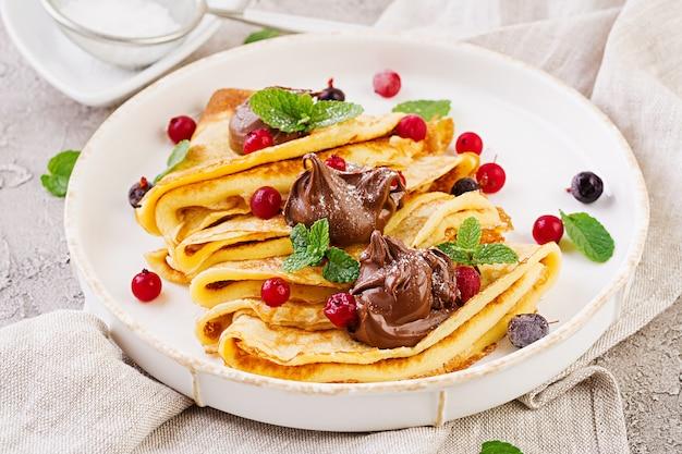 Pancakes con frutti di bosco e cioccolato decorati con foglie di menta. gustosa colazione