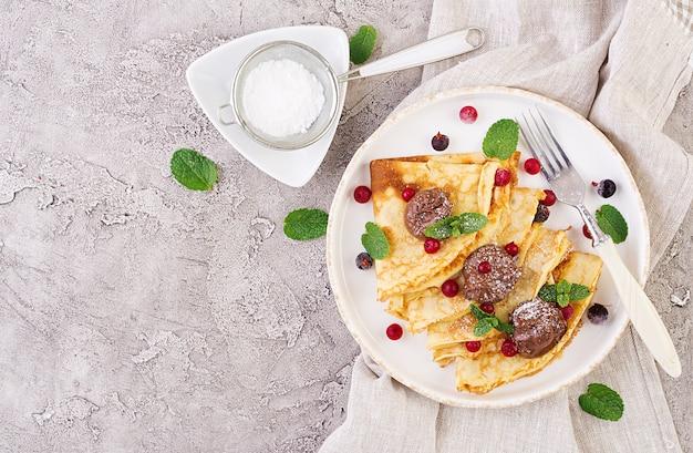 Pancakes con frutti di bosco e cioccolato, decorati con foglie di menta