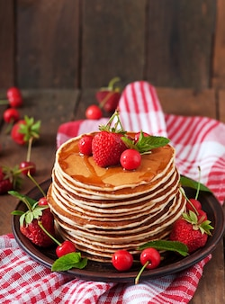 Pancakes con frutti di bosco e sciroppo in stile rustico