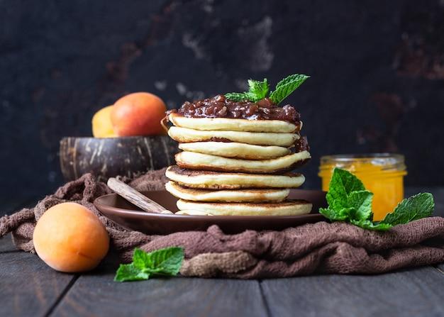 Pancakes con marmellata, albicocca e menta. delizioso dessert per colazione.