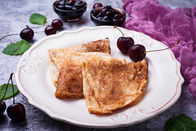Pancakes con marmellata di ciliegie e frutti di bosco. messa a fuoco selettiva