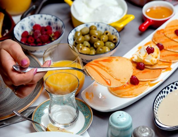 Pancakes con marmellata, olive, un bicchiere di succo e lamponi