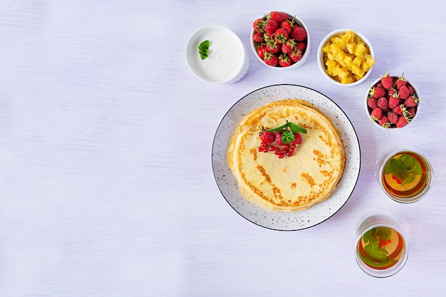 Pancakes con mele caramellate, lamponi, fragole e ribes rosso
