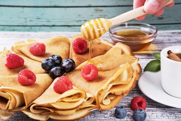 Pancakes con miele e frutti di bosco freschi lamponi e mirtilli