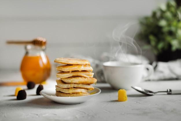 Pancakes con miele e una tazza di tè
