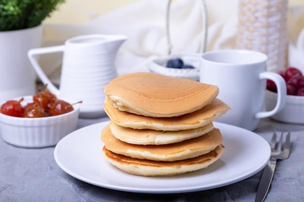 Pancakes con mirtilli, ciliegie e mini marmellata di mele. una tazza di caffè e una salsiera in background. pancakes americani tradizionali. avvicinamento.