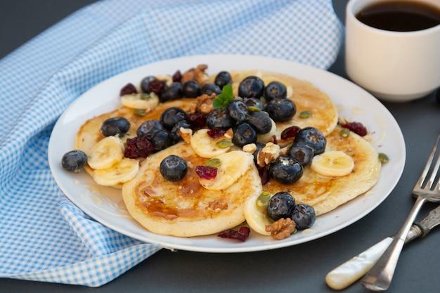 Pancakes con mirtilli, frutta secca e miele. colazione con caffè e pancake.