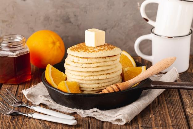 Pancakes in padella con mestolo e barattolo di miele