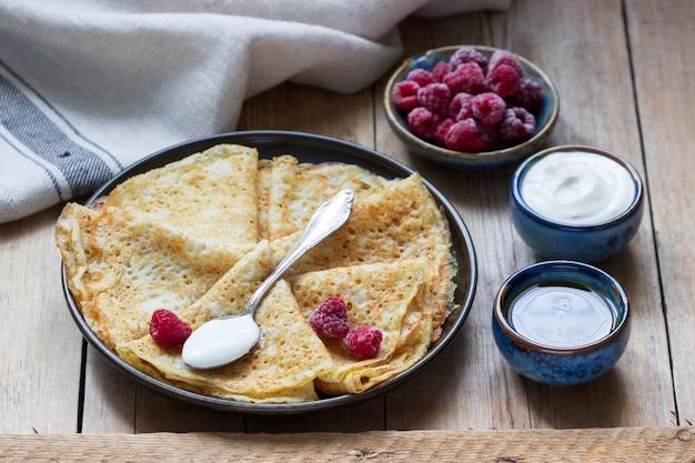 Pancakes serviti con panna acida, lamponi e miele. il piatto tradizionale di carnevale e maslenitsa.