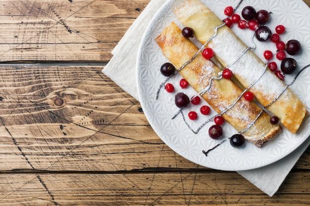 Pancakes tubo con cioccolato e frutti di bosco su un piatto. fondo in legno copia spazio