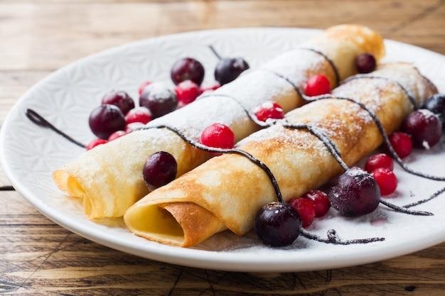 Pancakes tubo con cioccolato e frutti di bosco su un piatto. fondo in legno