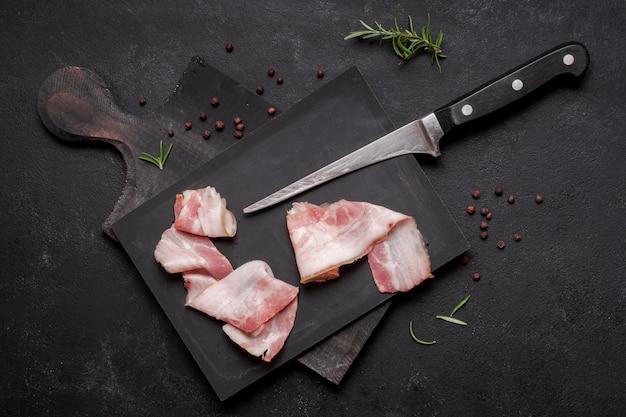 Pancetta affumicata cruda fresca sul bordo di legno con il coltello