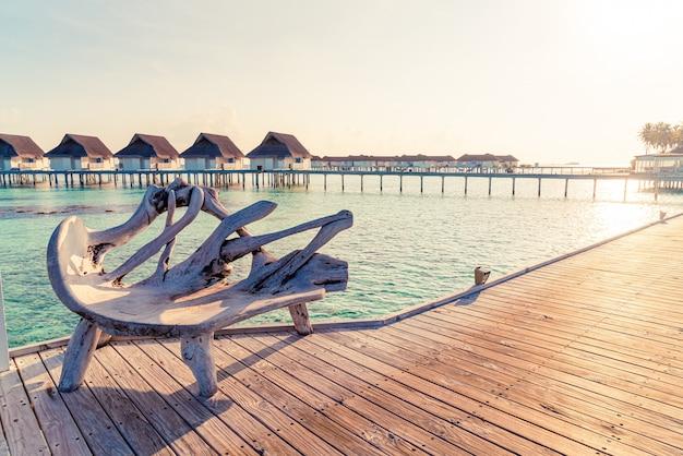 Panchina con resort tropicale delle maldive e mare