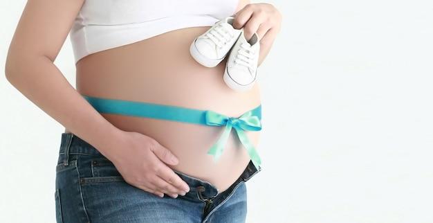 Pancia della donna di gravidanza con il nastro blu e le scarpe di bambino